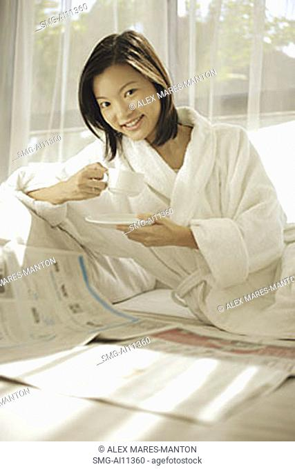 Young woman drinking coffee, newspaper open in front of her