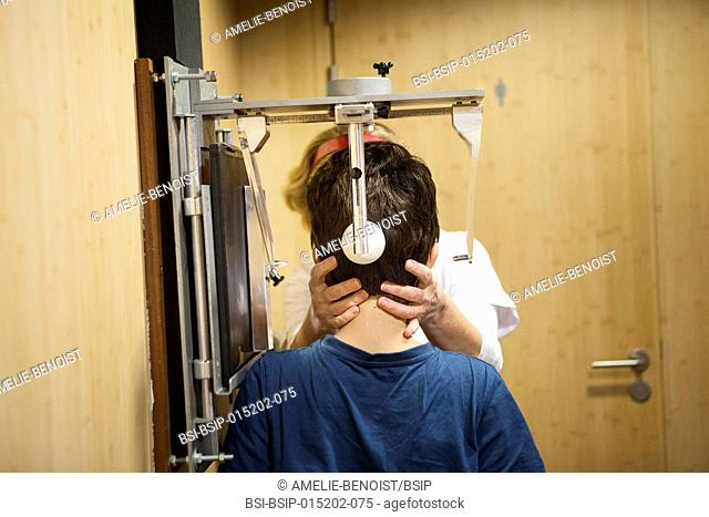 Reportage in a radiology centre in Haute-Savoie, France. A technician positions a young patient for a cranial x-ray