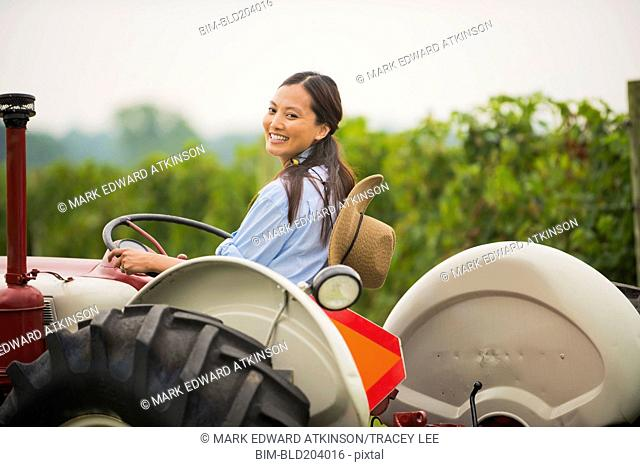 Asian woman driving tractor in field