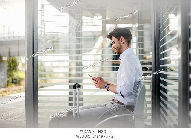 Businessman sitting on station platform using cell phone