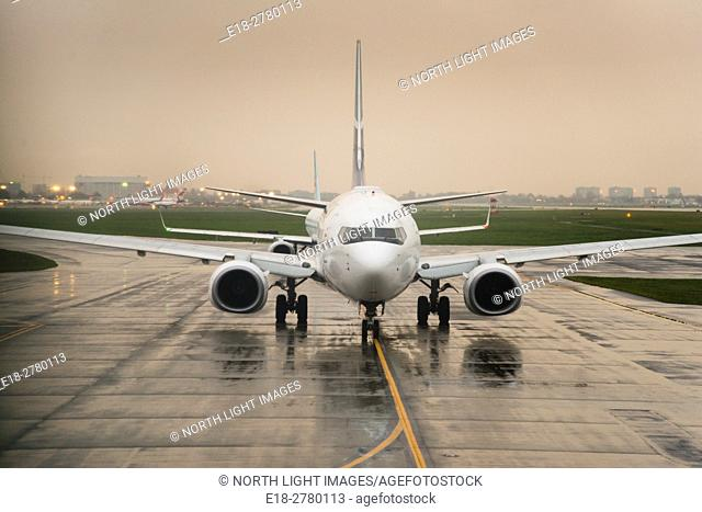 USA, IL, Chicago. Passenger jet prepares for takeoff on wet runway at O'Hare International Airport