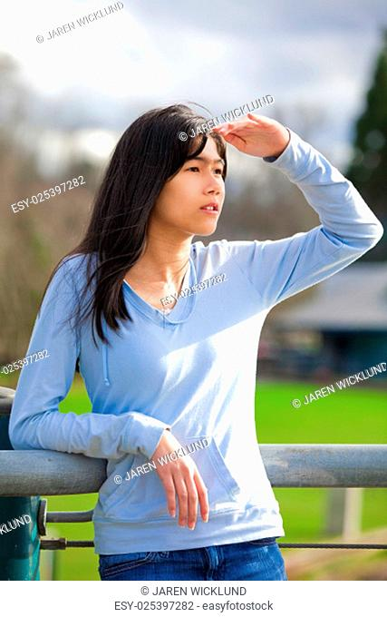 Young biracial teen girl standing, leaning against railing at park shading eyes to look off to side