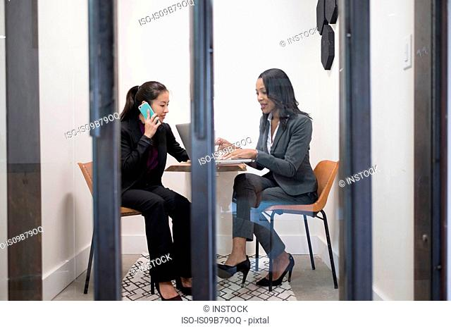 Two businesswomen in office, using laptop, talking on smartphone