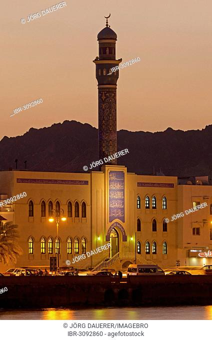 Floodlit buildings at the Corniche of Muttrah dominated by the minaret of the Rasool Azam Mosque