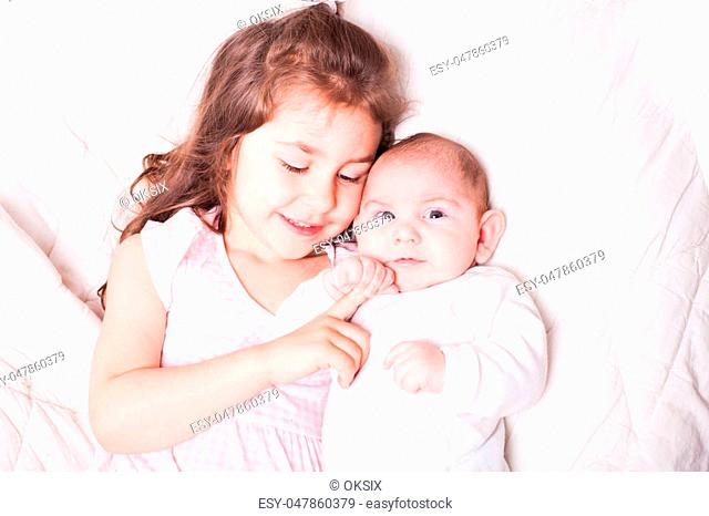 Pretty little girl laying with her adorable brother on the soft background