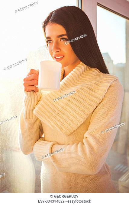 Beautiful girl near the window with a cup in hand at home