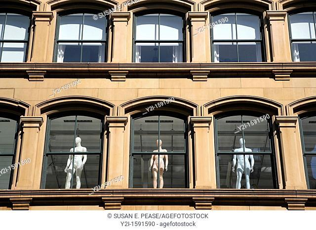 Human figures stand in the windows of a building in Manhattan's Soho neighborhood  Soho, Manhattan, New York City, United States