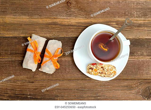 Top view on cup of tea and few bar of muesli. Brown wooden background