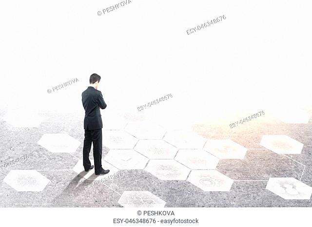 Thoughtful young businessman with white business interface on concrete ground and bright background with copy space. Research and media concept