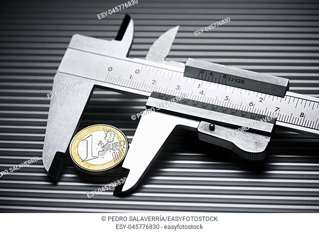 metal gauge measuring a one euro coin on a metal surface