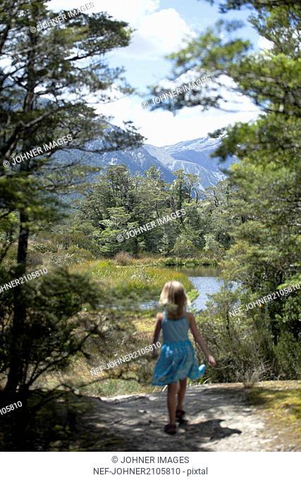Small girl walking towards lake