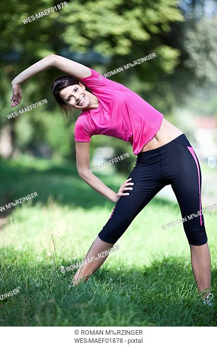 Germany, Bavaria, Woman stretching on meadow