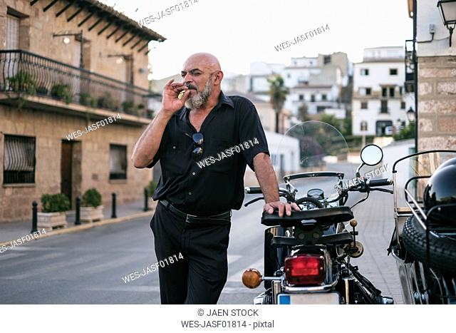 Spain, Jaen, mature man smoking next to motorcycle with a sidecar