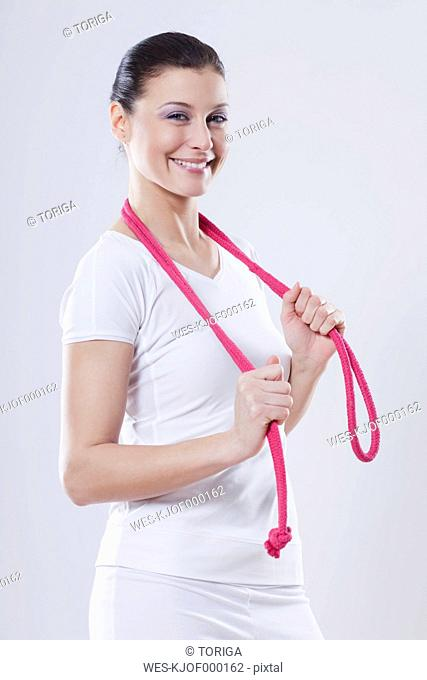 Close up of mid adult woman with rubber rope against white background, smiling, portrait
