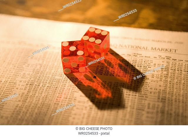 Close up of dice sitting on stock market paper