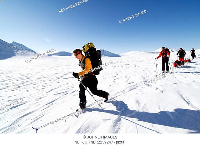 Tourists cross country skiing in mountain scenery