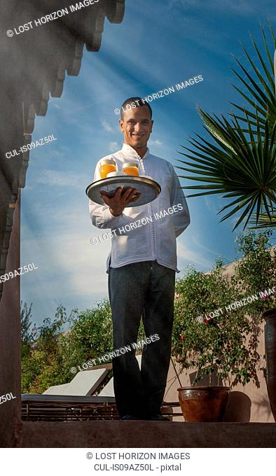 Waiter holding tray of drinks looking at camera smiling, Marrakesh, Morocco