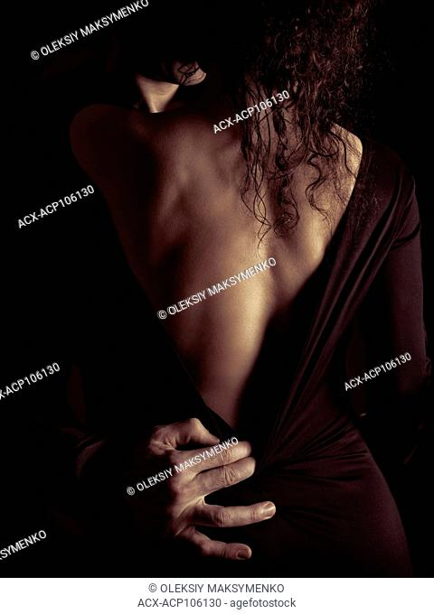 Sensual romantic portrait of a couple kissing, a man and a woman in a black dress with a low cut revealing her back