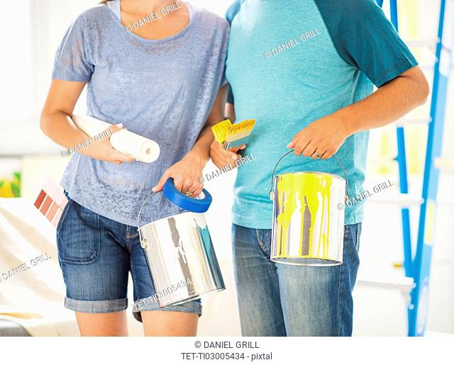 Mid section of couple with paint rollers and paint cans