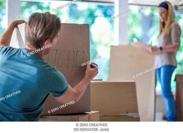 Moving house: man writing on cardboard box