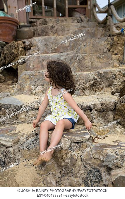 Fun fashion lifestyle portrait of a young three year old girl sitting on some stone stairs at the beach in Oahu Hawaii