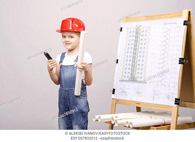 Girl playing Builder talking on the phone behind the blackboard with a drawing of a house