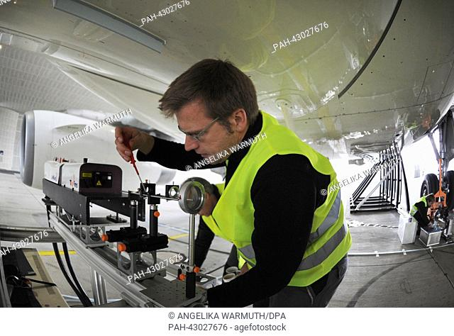 Employees work under the research aircraft A320-ATRA in the aviation noise protection hangar at Lufthansa Technik in Hamburg,Germany, 28September 2013