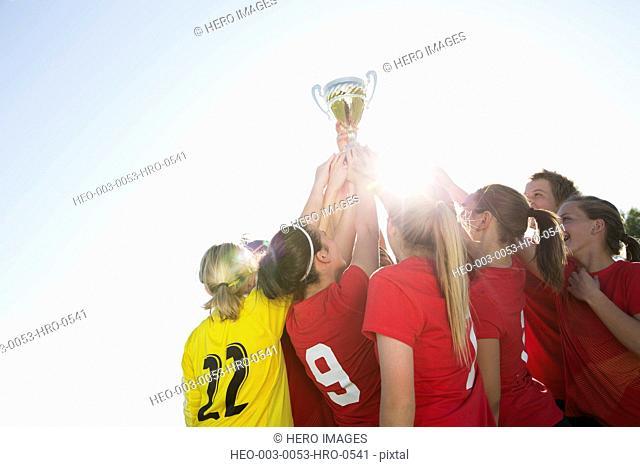 Soccer girls lifting trophy in celebration