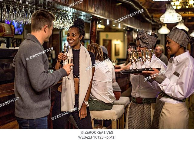 Couple having a glass of champagne in a bar