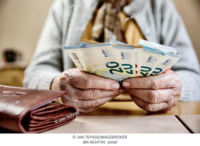 Hand of a senior citizen with euro notes, senior citizen counts her money, Germany