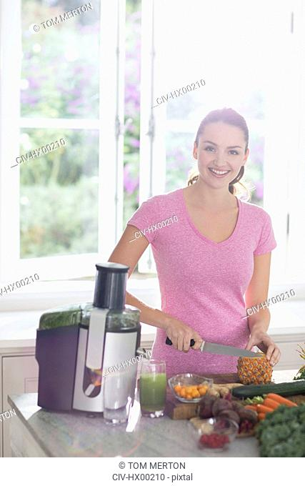 Portrait smiling woman slicing pineapple for juice
