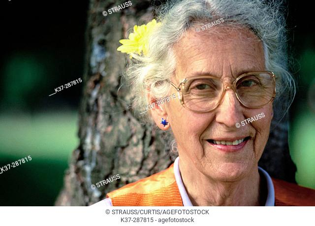 Senior woman with flower in hair and glasses