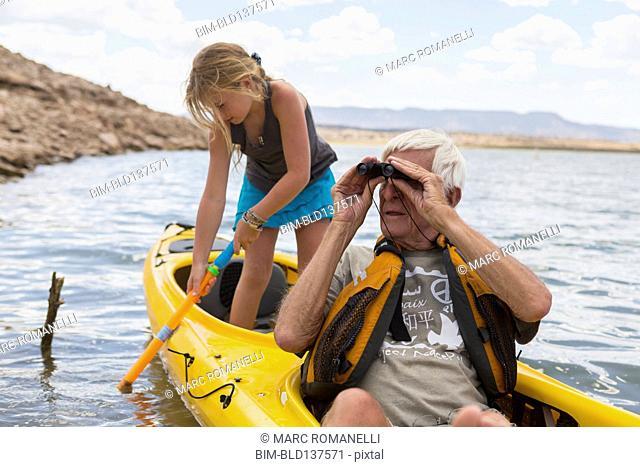 Older Caucasian man in kayak with granddaughter