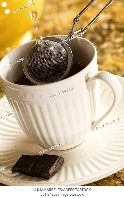 STILL LIFE Pouring hot water through mesh strainer for loose leaf tea over cup and saucer, tea pot, piece of dark chocolate