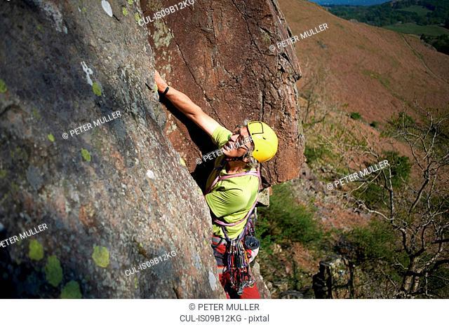 High angle view of rock climber climbing rock face