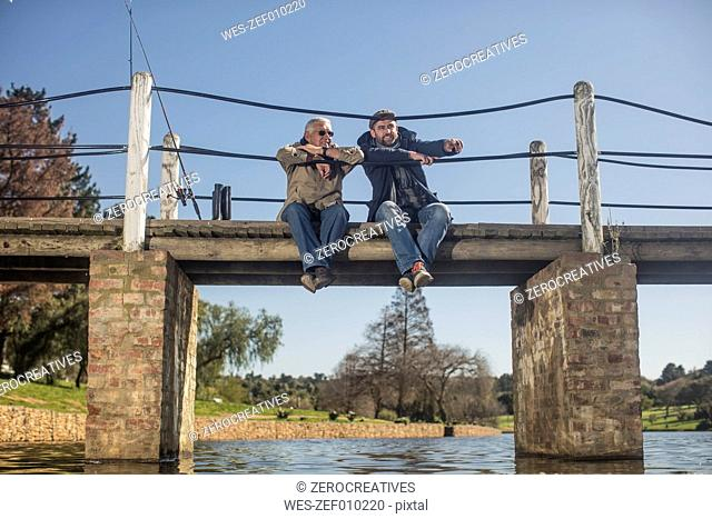 Senior man and adult son sitting on a bridge fishing together