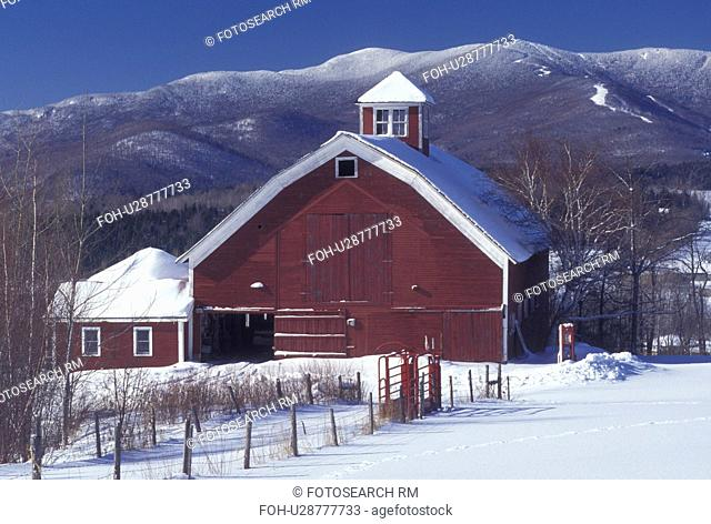 barn, Vermont, VT, Mad River, Scenic view of red barn in Warren in the Mad River Valley in winter with the snow-covered Green Mountains and Sugarbush Ski Area...