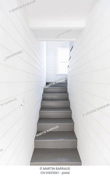 Gray stairs between whiteboard walls