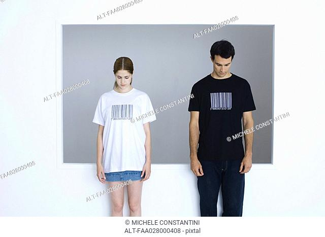 Two young adults wearing tee-shirts printed with bar codes, both looking down