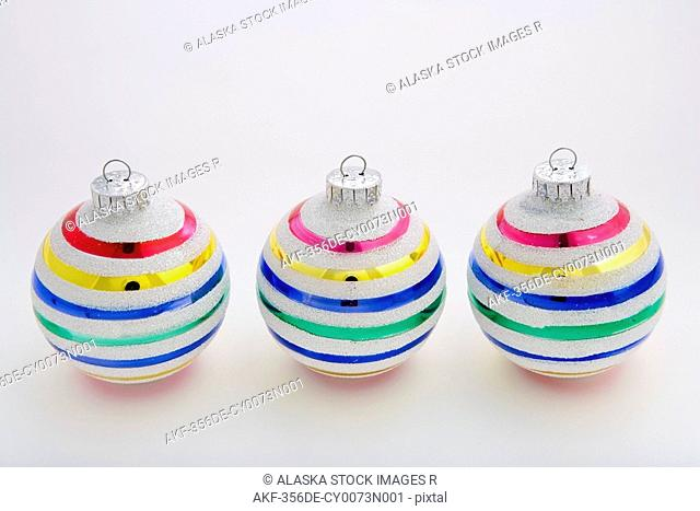 Three striped Christmas tree balls in line on white background in studio portrait