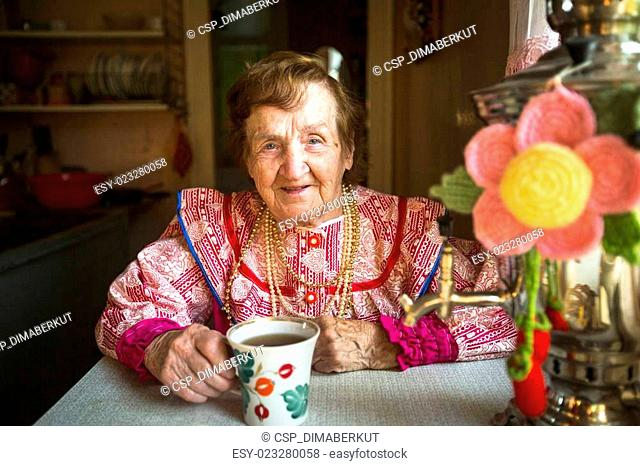 Elderly woman in ethnic clothes drinking tea in his house