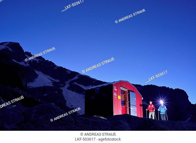 Two persons hiking towards illuminated red bivouac, bivouac Molteni, Sentiero Roma, Bergell range, Lombardy, Italy
