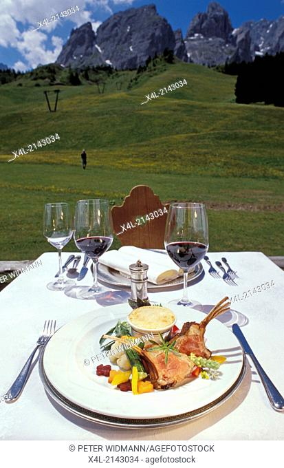 table set with red wine, meat dish on a terrace, in the background beautiful mountain scenery
