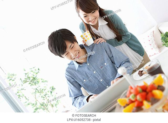 Dining Table, Couple Using Laptop In Background