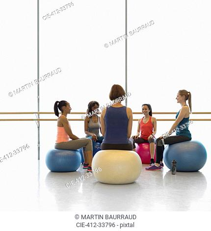 Women on fitness balls in circle in exercise class gym studio