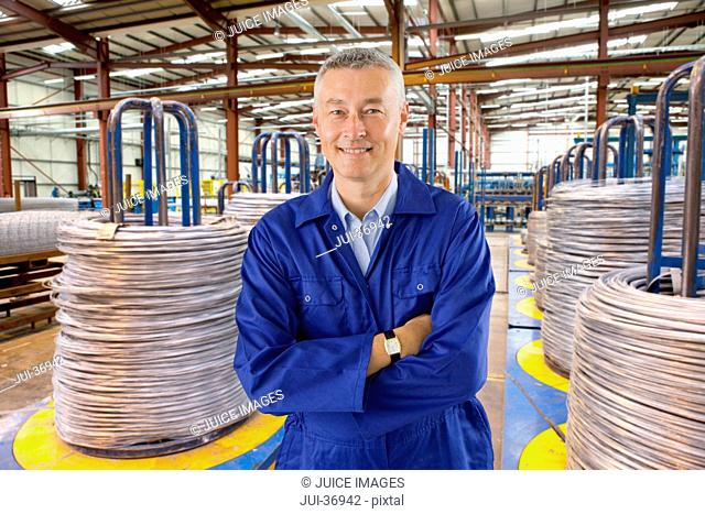 Portrait of smiling worker in coveralls standing among coiled cable in warehouse