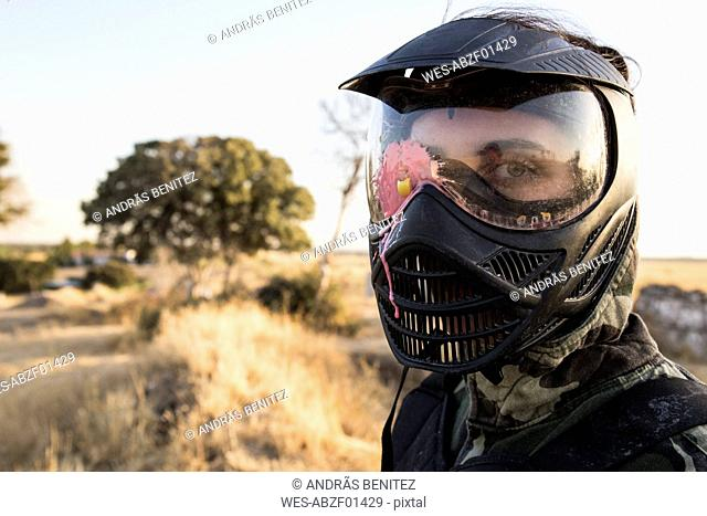 Female paintball player with paintball mask stained with paint