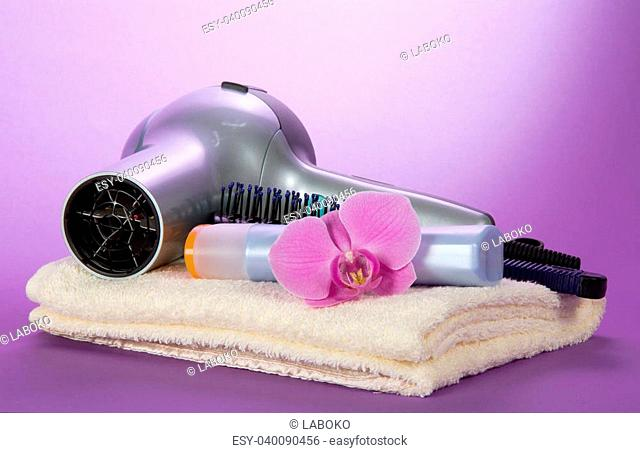 The hair dryer, hairbrush, shampoo on a towel, decorated with a flower, on the violet