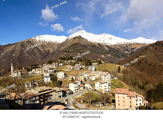 landscape with mountain village among high peaks of Bergamo mountains in a winter with little snow , shot with blue sky in bright winter light