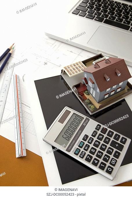 Architectural model, a calculator, and a tablet PC